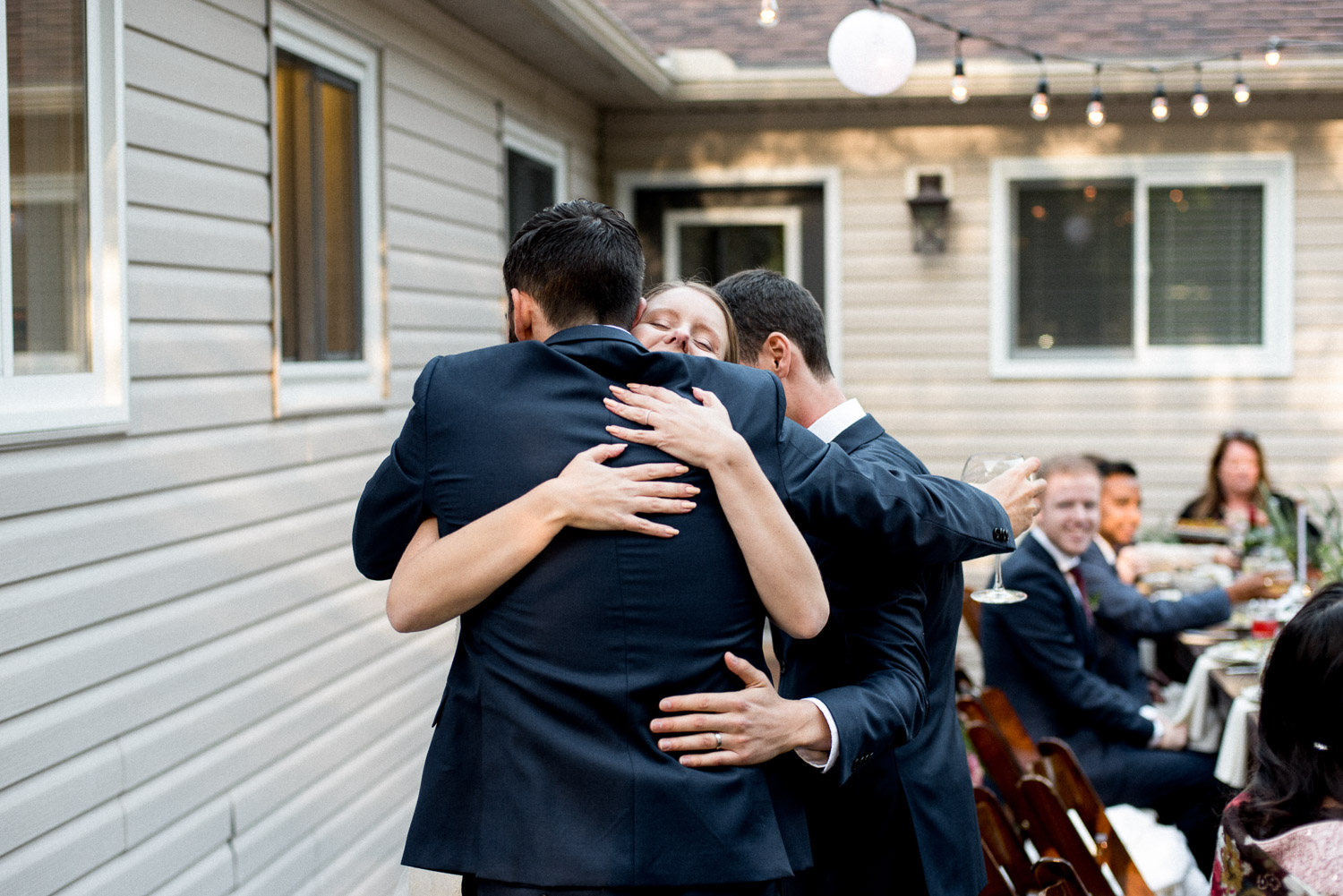 bride and groom hugging wedding guest
