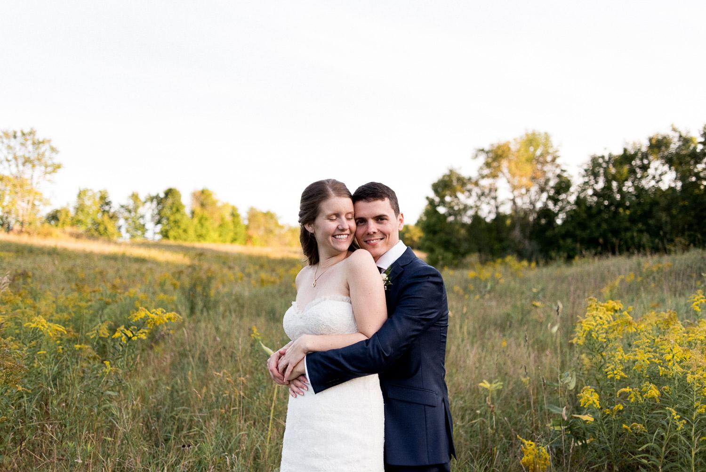 happy couple snuggling in a field