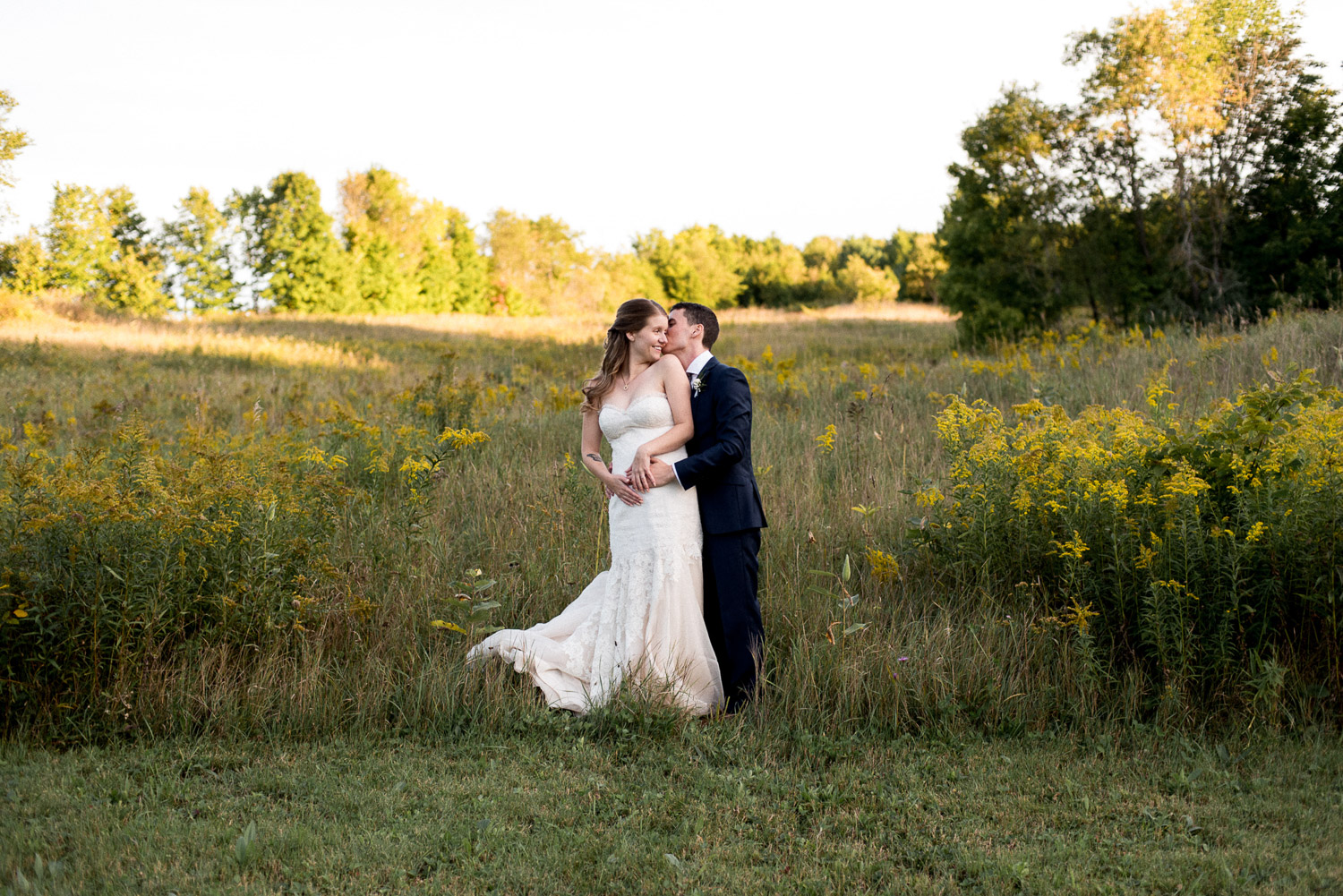 bride and groom snuggle in a field