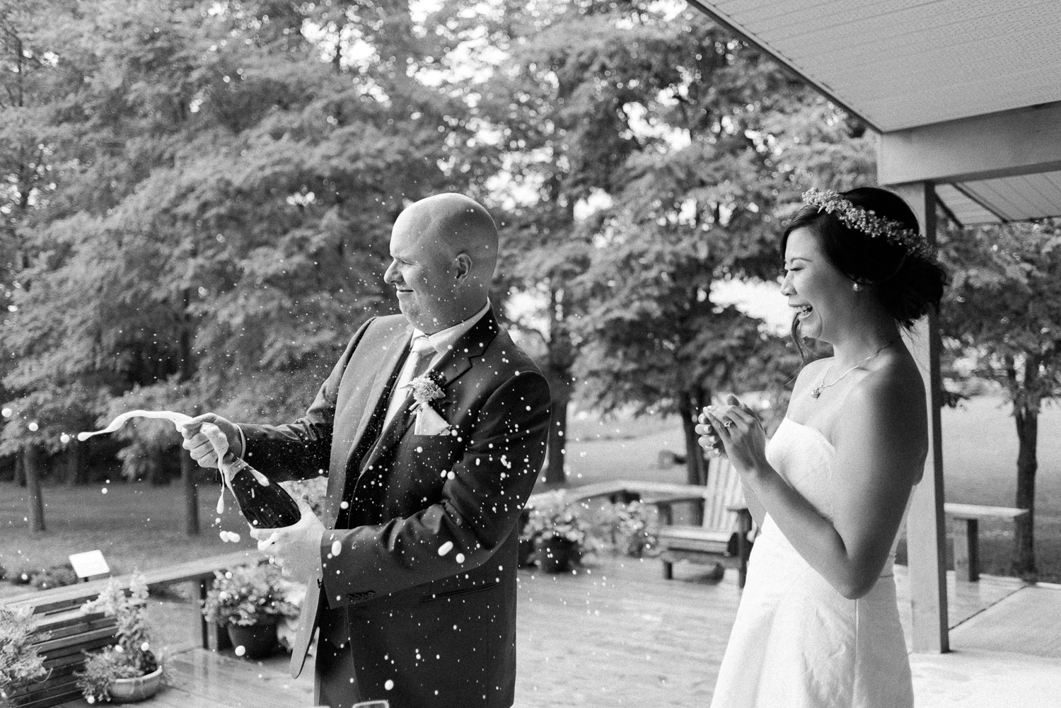 couple popping champagne bottle at their elopement