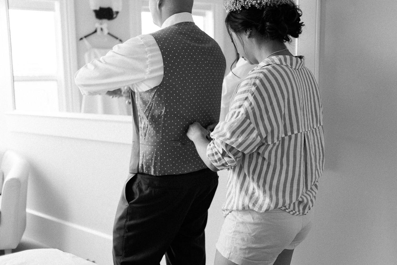 bride tightening groom's vest